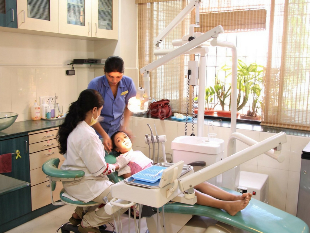 women dental professionals working on a pediatric patient