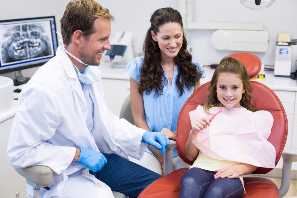 Dentist assisting young patient to brush teeth