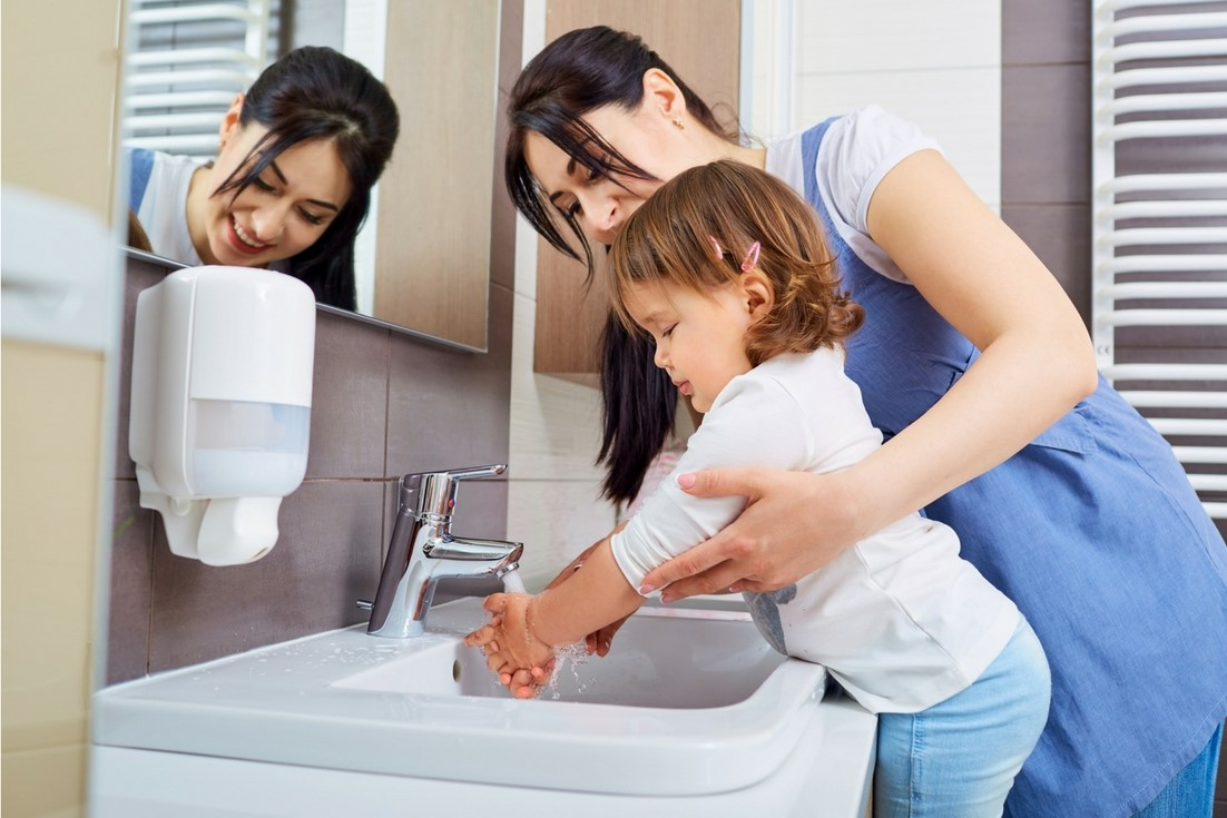 parent helping child wash hands