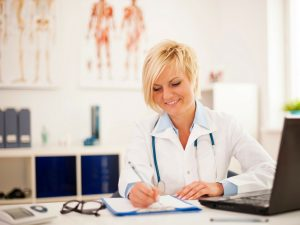 female medical professinal at computer with clipboard