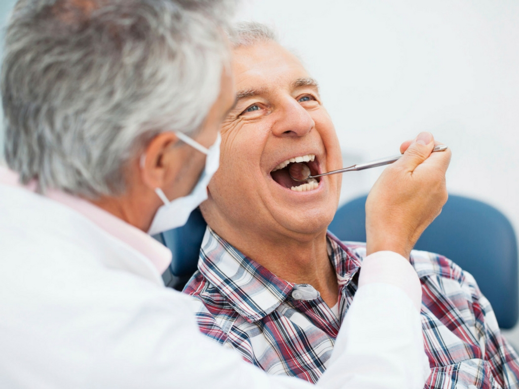 male dentist with older male patient