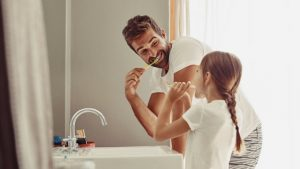 little girl brushing teeth with dad