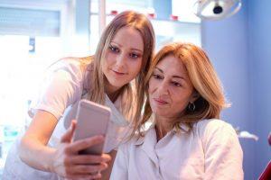 dental assistant showing dentist smartphone