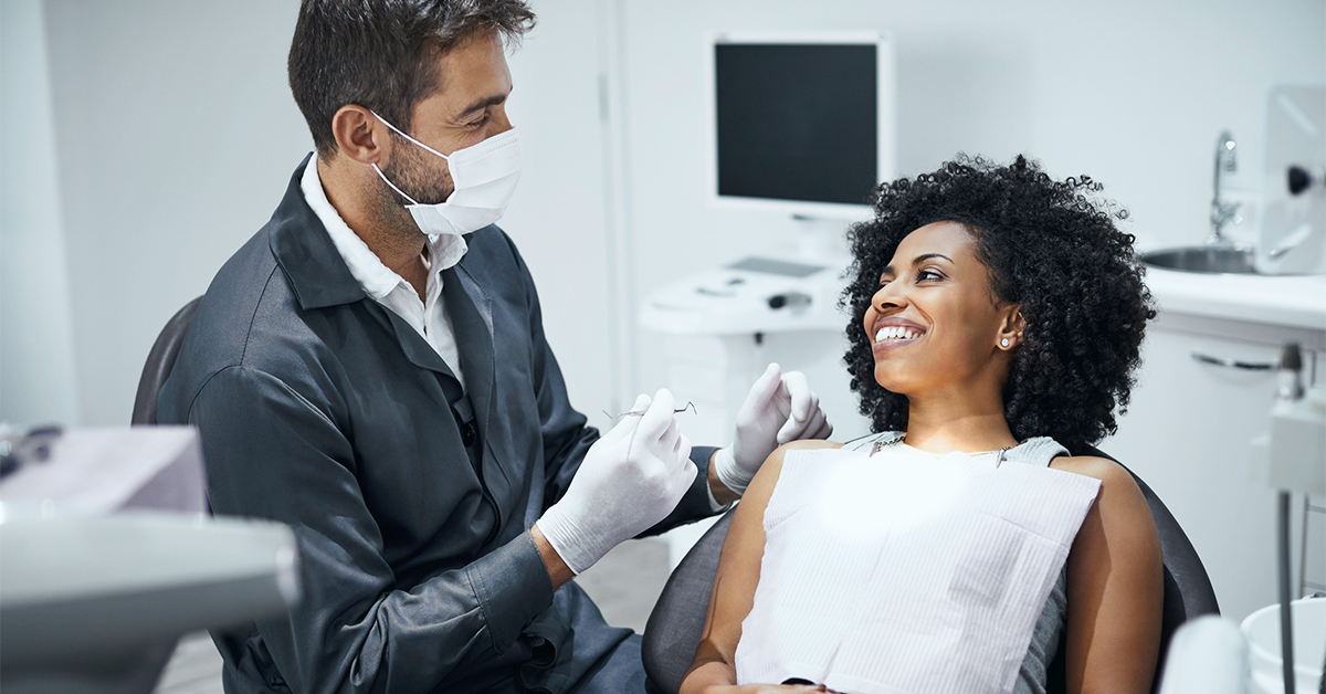 A dentist consults a patient.