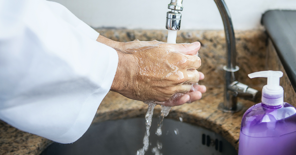 Dentist washing hands with soap and water.