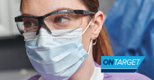 Dental hygienist with face mask and protective eyewear.